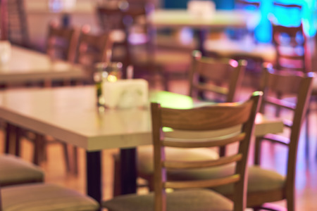 Blurred restaurant or cafe background. Tables and chairs in the lobby of the mall. Visitors to the restaurant for dinner. Beautiful bright interior Imagens