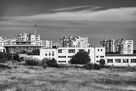 Old houses in a poor neighborhood. City quarter in black and white.  Gray gloomy clouds in the sky. Basic bright heaven background for design 스톡 콘텐츠