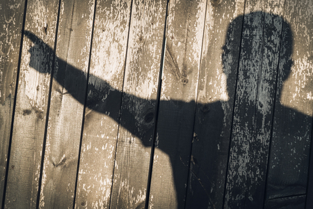 The shadow of a man on wooden boards. Raised hand in greeting shows provocation indecent