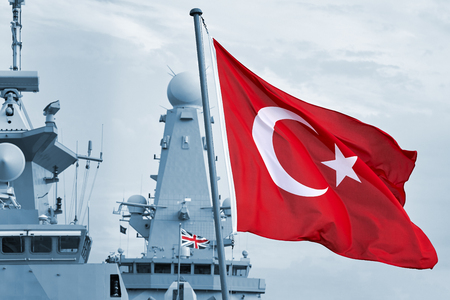 Maritime city port. Fragment of a warship on the quay on the sunset. Guns aboard the ship. The flag of Turkey fluttering in the wind. Waves at sea