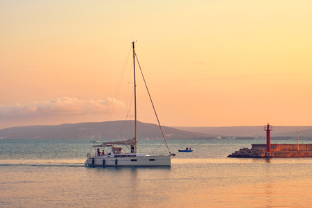 Pleasure yacht in the sea harbor against the backdrop of the orange sunset sky. The family skates on a beautiful yacht in the summer
