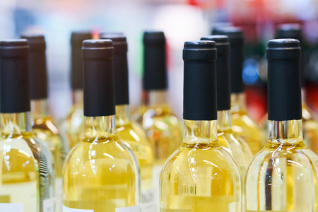 Blurred  bottles of white and rose wine are nicely laid out in a row on a shelf in a large supermarket. Bright abstract background ideal for any design