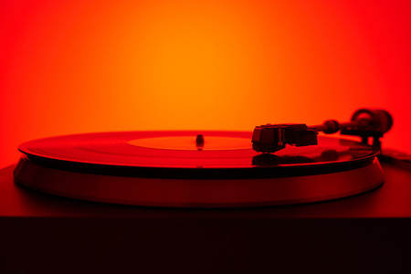 Turntable vinyl record player in the red light. Retro audio equipment for disc jockey.