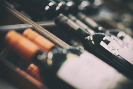 Bastidores borrosos con botellas de vino tinto. Estantes con botellas de vino en un gran supermercado de abarrotes. Antecedentes básicos para el diseño.
