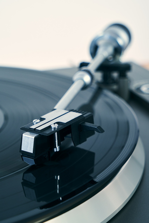Detail of a turntable vinyl record player. Sound technology for DJ to mix & play music. Black vinyl record. Needle on the plate.  Bright background for the basic design Stock Photo