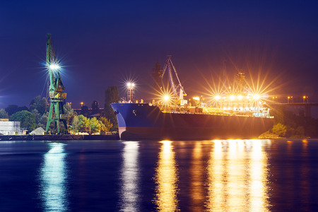 The seaport at night. Cargo ship loading in port. Loading cranes. Bright light of street lamps. Waves at sea