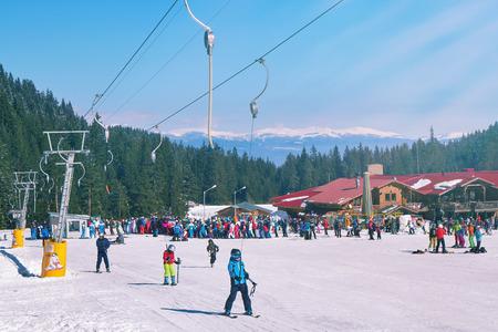 Bansko, Bulgaria - Circa February 2017: Mountain. Skiers climbing on the piste. Ski resort. Ski track. People ski on snow in the winter. Pine forest