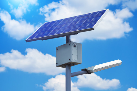A city electric lantern on a solar battery in a park on a summer day against a blue sky background close-up