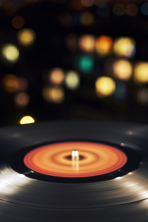 Turntable vinyl record player on the background of a sunset over the lights city. Sound technology for DJ to mix & play music. Black vinyl record. Vintage vinyl record player. Needle on a vinyl record Standard-Bild