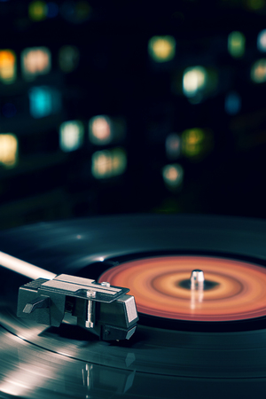 Turntable vinyl record player on the background of a sunset over the lights city. Sound technology for DJ to mix & play music. Black vinyl record. Vintage vinyl record player. Needle on a vinyl record Stock Photo