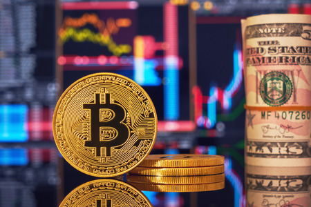 Golden bitcoin are stacked on a bright background of business graphs close-up. Bitcoin cryptocurrency. Folded in a tube 100 dollar bills