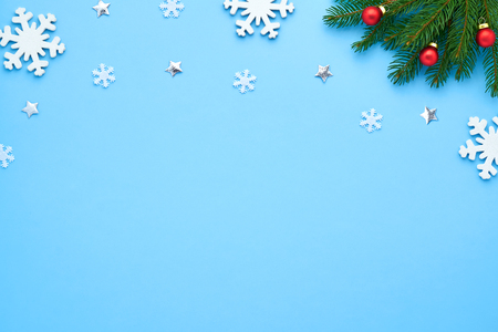 Christmas card. Blue background with figures of white snowflakes, shiny stars. Brushing a branch of a tree with red balls. Background for your text and design Stock Photo