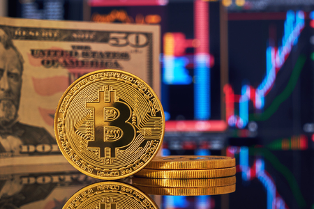 Golden bitcoin are stacked on a bright background of business graphs and 50 dollar bills close-up. Bitcoin cryptocurrency. Anonymous Фото со стока