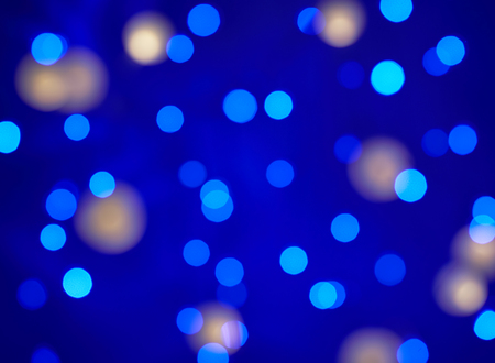 Blur bright multicolored lights on a blue background. Christmas texture for greeting cards. A ready-made idea for your design and text
