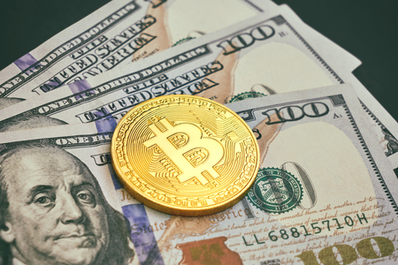 Beautifully arranged bills 100 dollar and gold coin bitcoin on a gray background. Bitcoin cryptocurrency. Anonymous. Background for your text and design
