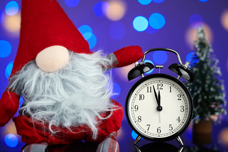 New Years picture. A vintage alarm clock on a background of bright blurred festive lights.