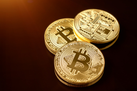 Gold bitcoin coin stacked against a dark background close-up. Bitcoin cryptocurrency. Anonymous Stock Photo