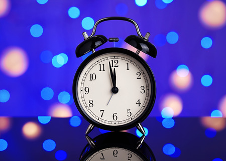 New Years picture. Vintage alarm clock on a background of bright blurred festive lights. A bright abstract background is perfect for any design.