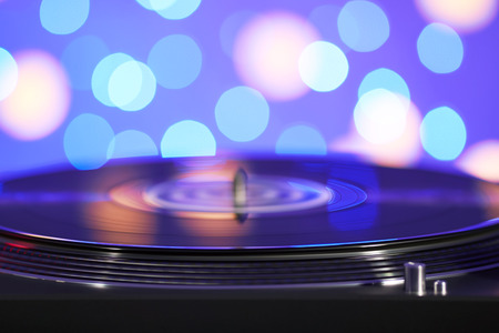 Blurred turntable vinyl record player. Sound technology for DJ to mix & play music. Vintage vinyl record player on a background decorations for a party, bright disco lights