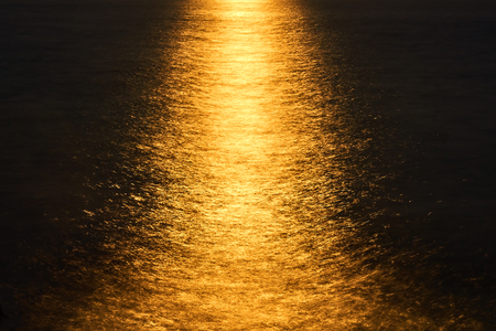 Night seascape. Beautiful, bright reflection of the moon on the surface of the sea of golden color