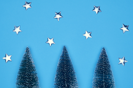 Christmas card decorated with three Xmas fir-trees, shiny stars on a blue background Stock Photo