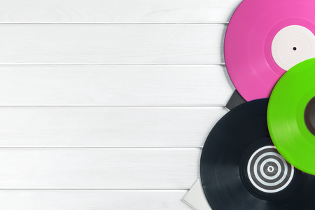 Festive postcard frame. Background of vinyl records DJs for a music player on a white wooden background close-up. Green, black, pink vinyl records. Turntable audio equipment for disc jockey Foto de archivo - 97466407
