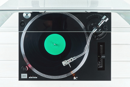 Turntable vinyl record player on the background of their white wooden boards. Sound technology for DJ to mix & play music. Needle on a vinyl record. Black vinyl record