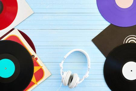 Festive postcard frame. Background of vinyl records DJs for a music player white headphones on a blue wooden background close-up. Red, black, purple vinyl record Foto de archivo - 97456627