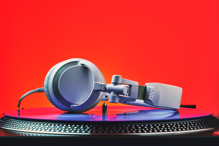 Player turntable vinyl records and white headphones in red light. Equipment for the disc jockey. Sound technology for DJ to mix and play music. Violet vinyl plate. Vinyl turntable in red light Stock Photo