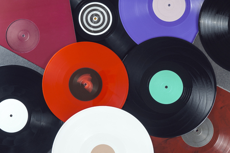 Background of vinyl records DJs for a music player close-up. Red, black, white vinyl records. Turntable audio equipment for disc jockey. Sound technology for DJ to mix & play music Foto de archivo - 97466052