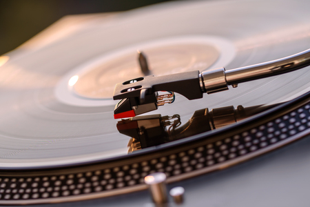 Turntable vinyl record player on the background of a sunset over the lights city. Sound technology for DJ to mix & play music. Black vinyl record. Vintage vinyl record player. Needle on a vinyl record Stok Fotoğraf