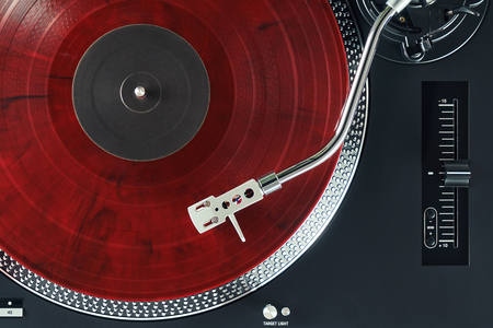 Turntable vinyl record player. Sound technology for DJ to mix & play music. Needle on a vinyl record. Red vinyl record