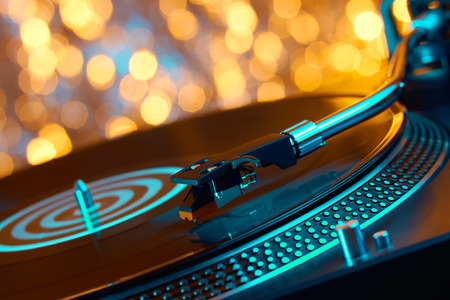 Turntable vinyl record player. Sound technology for DJ to mix & play music. Vintage vinyl record player on a background decorations for a party, bright disco bokeh lights. Needle on a vinyl record