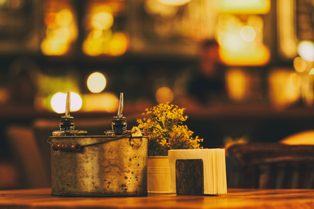 Beautiful restaurant design. Bright interior and lighting. Table in an institution with spices, vinegar and olive olive, paper napkins and flowers in a vase