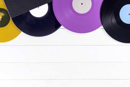 Holiday postcard frame. Background of vinyl records DJs for a music player on a white wooden background close-up. Red, black, violet  vinyl records. Turntable audio equipment for disc jockey Stock Photo