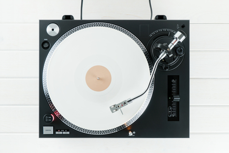 Turntable vinyl record player on the background white wooden boards. Sound technology for DJ to mix & play music. Needle on a vinyl record. White vinyl record