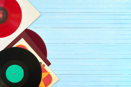 Festive postcard frame. Background of vinyl records DJs for a music player on a blue wooden background close-up. Red, black. Turntable audio equipment for disc jockey Foto de archivo - 97317629