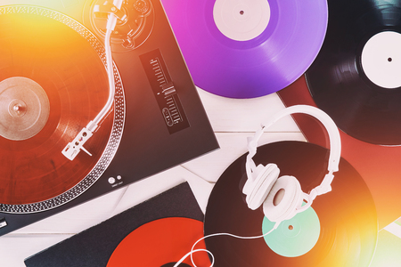 Turntable vinyl record player and white headphones on the background white wooden boards. Sound technology for DJ to mix & play music. Needle on a vinyl record. Red marble vinyl record Stock Photo