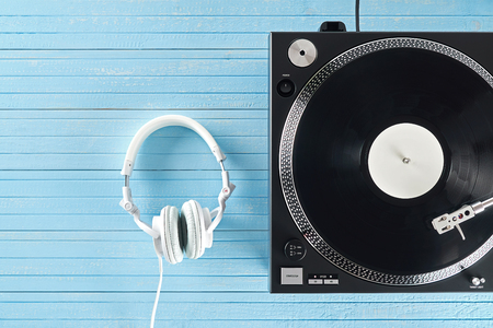 Turntable vinyl record player and white headphones on the background blue wooden boards. Sound technology for DJ to mix & play music. Needle on a vinyl record. Black vinyl record