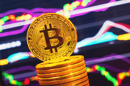Gold coin bitcoin stacked on a bright background of business graphics close-up. Bitcoin crypto-currency. Anonymous. Virtual currency