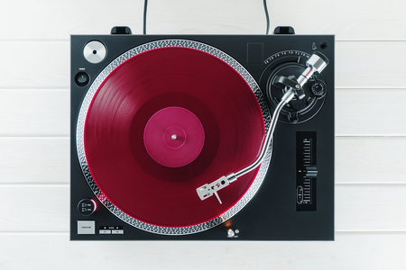 Turntable vinyl record player on the background white wooden boards. Sound technology for DJ to mix & play music. Needle on a vinyl record. Red vinyl record Standard-Bild
