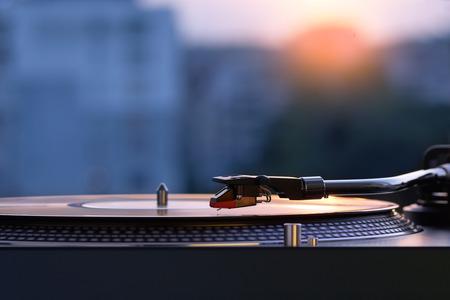 Platenspeler van de draaischijf vinyl op de achtergrond van een zonsondergang over de lichtenstad. Geluidstechnologie voor DJ om muziek te mixen en af te spelen. Zwart vinylplaat. Vintage vinyl platenspeler. Naald op een vinylplaat