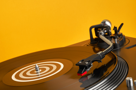 Turntable vinyl record player. Sound technology for DJ to mix & play music. Vinyl record player on a yellow background decorations for a party, bright disco lights. Need Stock Photo - 97242287