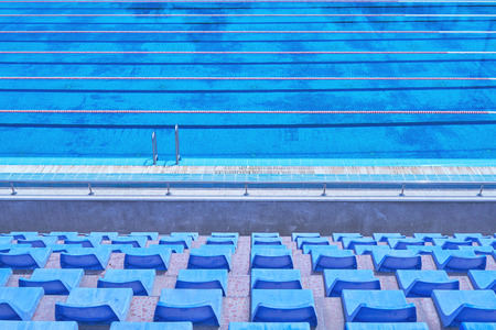Large urban sports pool for classes and competitions. Blue plastic seats for spectators and fans. Texture of blue water in the pool Stock Photo