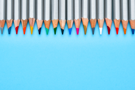 Texture of the school is delivered on a board close-up. Bright colorful pencils on a blue background. Ready background for design