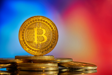 Gold coin bitcoin stacked on a bright red-blue background close-up. Bitcoin crypto-currency. Anonymous. Virtual currency