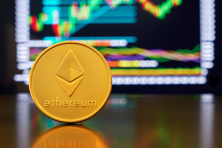 Gold coin ethereum stacked on a bright background of business graphics close-up. Crypto-currency ETH. Anonymous. Virtual currency