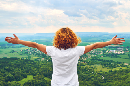 A young woman with red curly hair is standing with wide-spread arms and enjoying the beautiful view from a high point of the mountain. The tourist finished the sunrise to the top