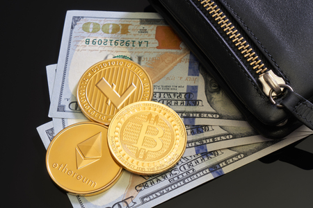 The man's black wallet lies on the background of paper bills of 100 dollar bills and three gold coins ripple, bitcoin, litecoin Crypto-currency. Anonymous. Virtual currency