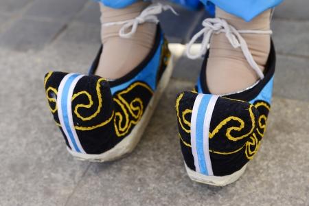 Een paar geborduurde schoenen aan mijn voeten